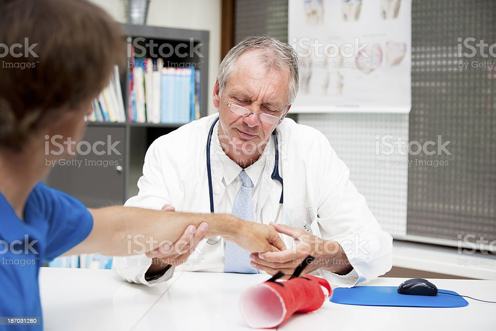 Mature medicine checking lower arm fracture stock photo