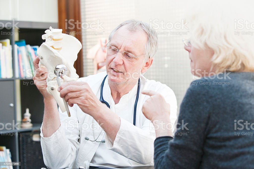 Mature medicine presenting total hip arthroplasty to female patient stock photo