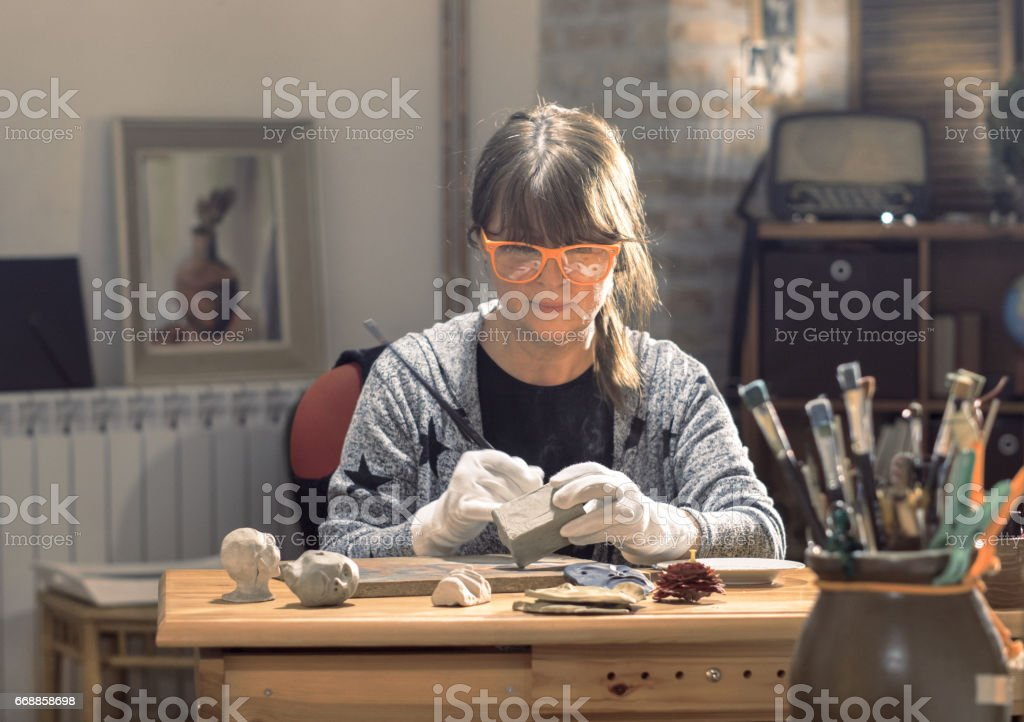 Mature middle aged artist moulding raw clay in art studio stock photo