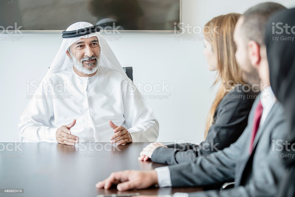 Mature Middle Eastern businessman wearing ghoutra in meeting stock photo