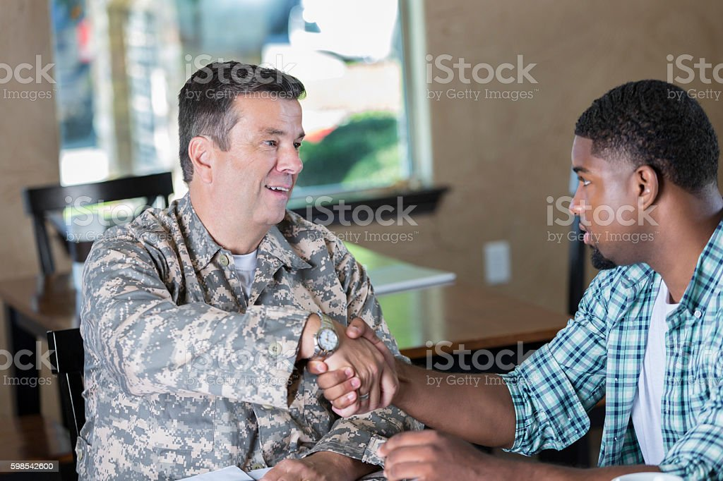 Mature military officer meeting with man in recruitment office stock photo