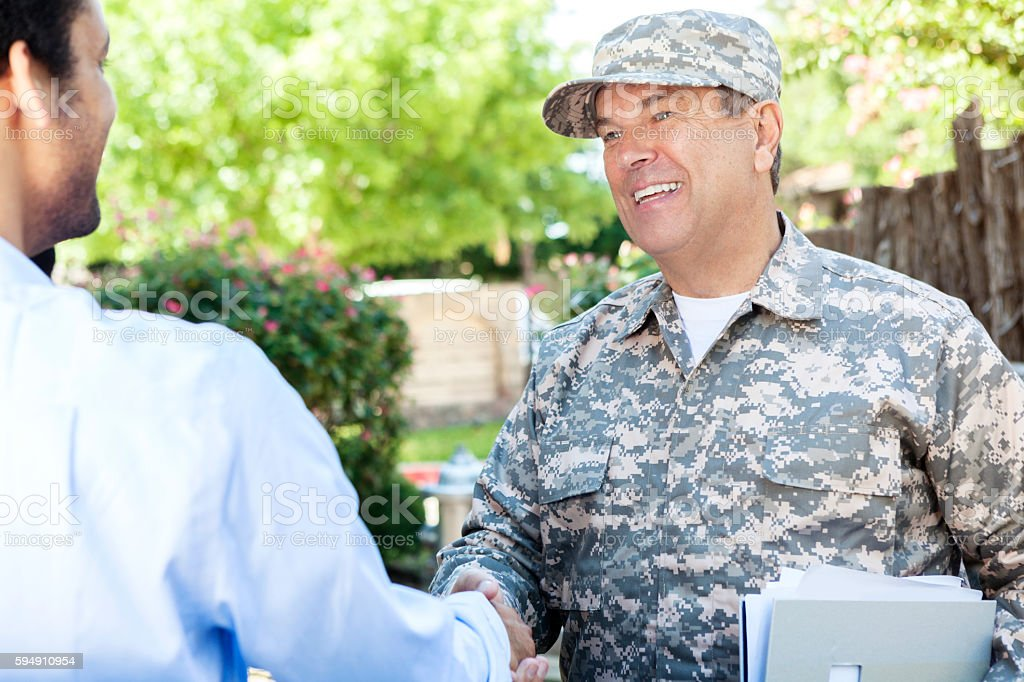 Mature military recruiter shaking hands with student to discuss enlistment stock photo