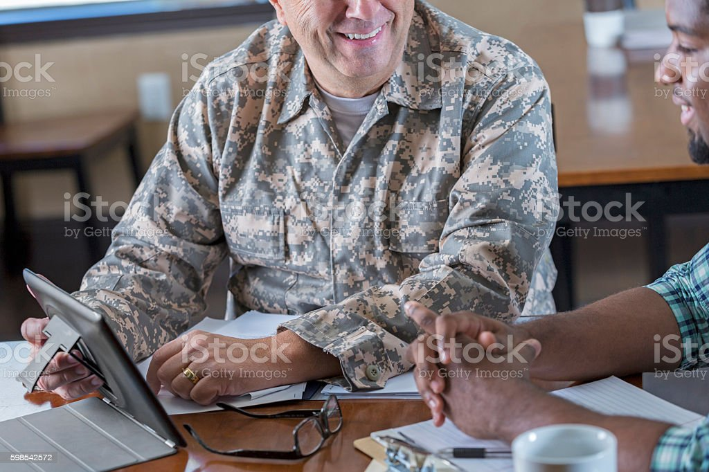 Mature military recruitment officer meeting with young man. stock photo
