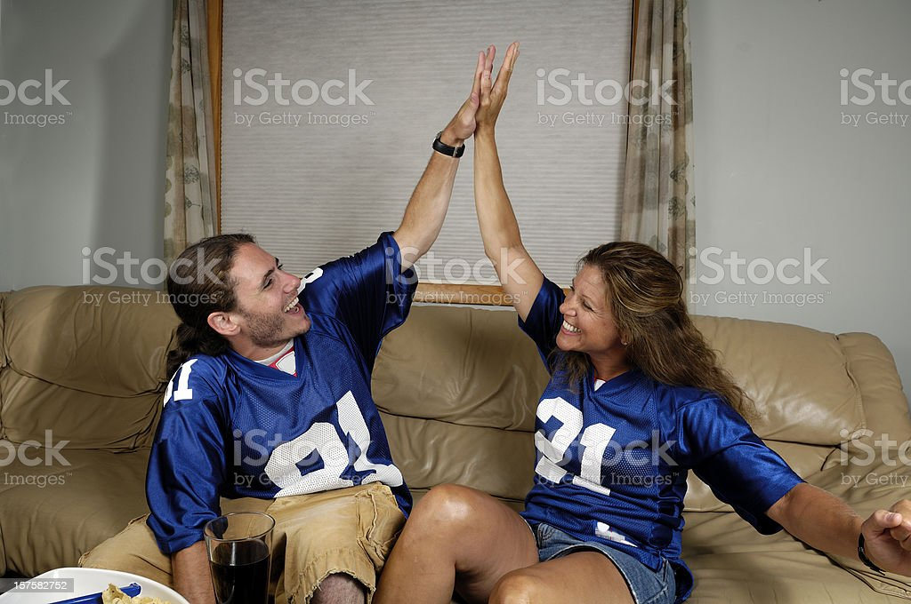 Mature mom and her teenage son watching a football game royalty-free stock photo