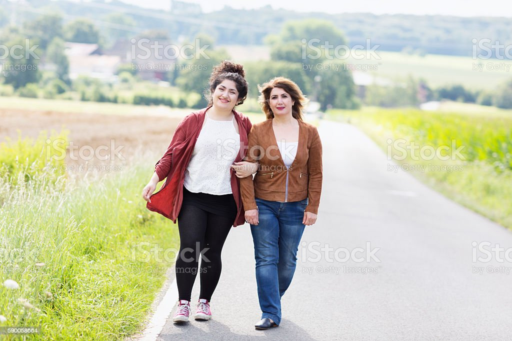 Mature mother and adult daughter walking together stock photo
