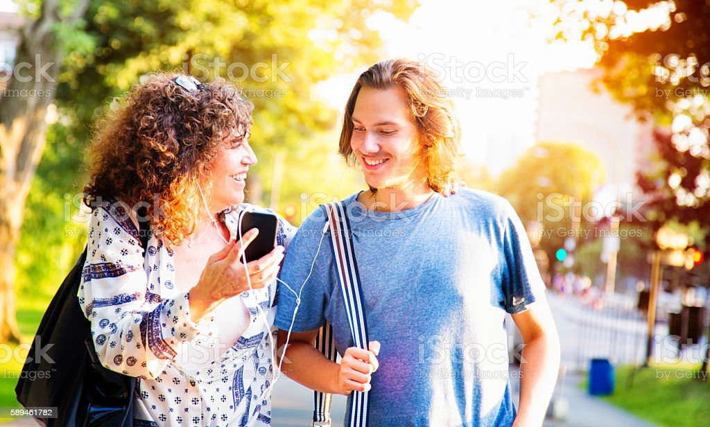 Mature mother shares music with teenage son using mobile phone stock photo