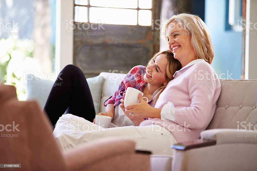 Mature Mother With Adult Daughter Watching TV At Home stock photo