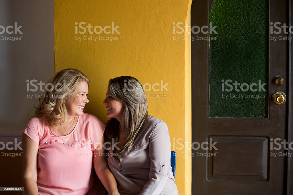Mature mother-daughter looking at each other stock photo