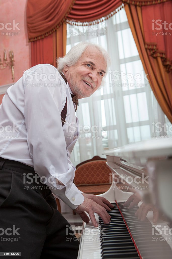 Mature musician playing a white piano stock photo