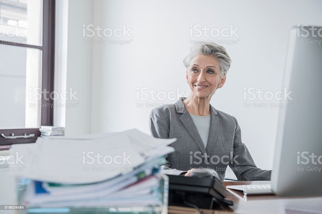 Mature office worker at desk looking away, smiling stock photo