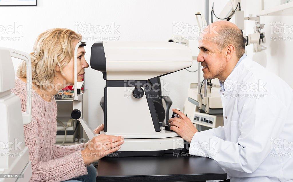 Mature optician examinating eyesight with aid of slit lamp stock photo