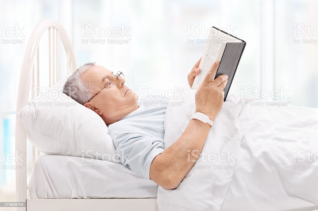 Mature patient lying in bed and reading a book stock photo