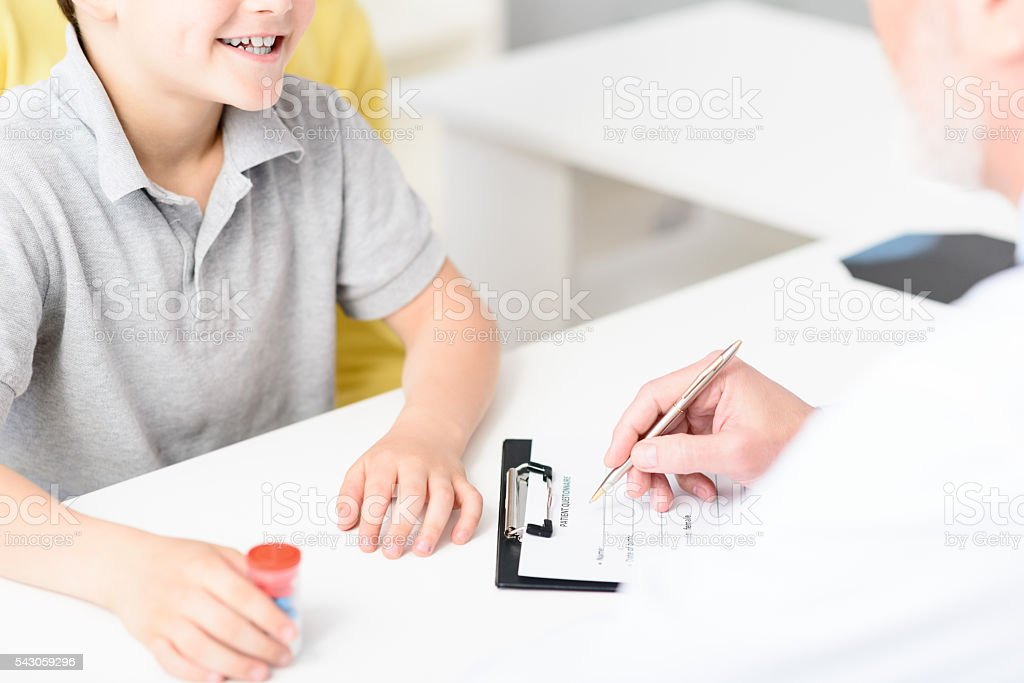 Mature pediatrician making recommendations for small patient stock photo