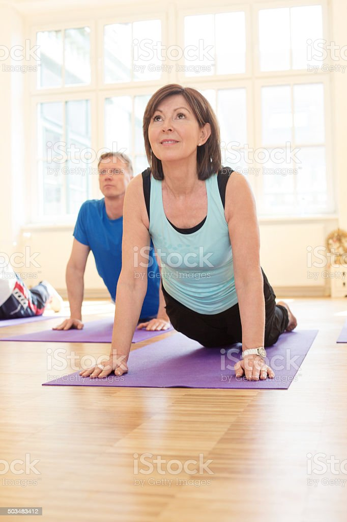 Mature people performing the cobra position in yoga class stock photo