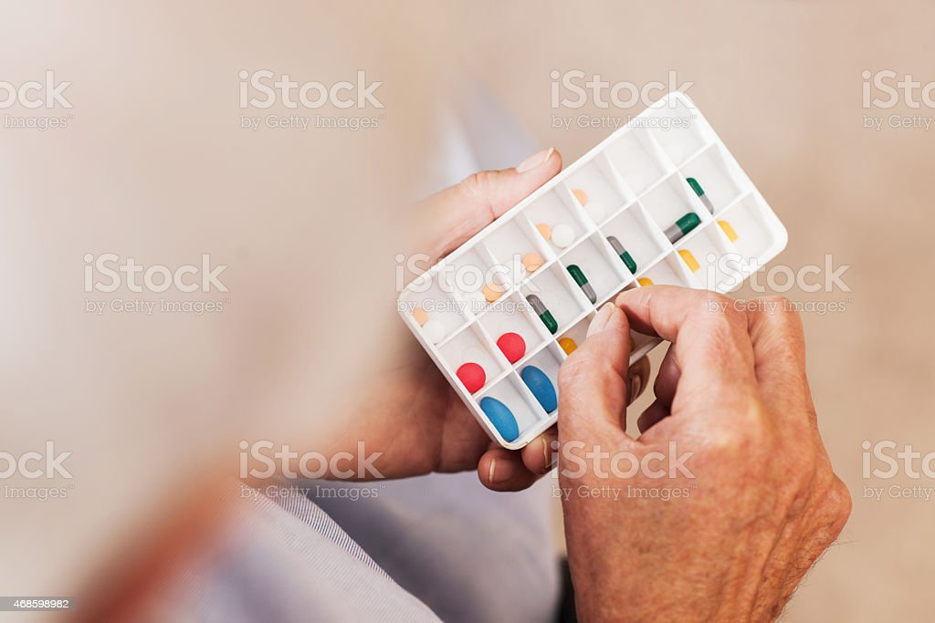 Mature person holding pills. stock photo