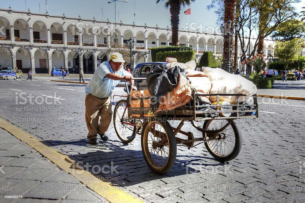 Mature Peruvian man pushing handcart on cobblestones royalty-free stock photo