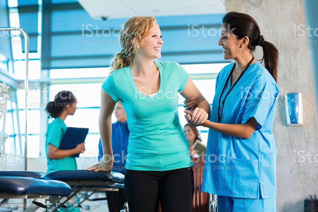 Mature physical therapist helping injured teenage girl to walk stock photo