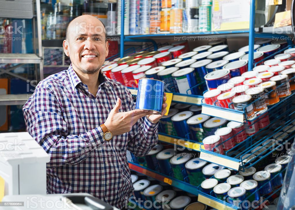Mature positive man selecting wall paint and emulsion in store stock photo