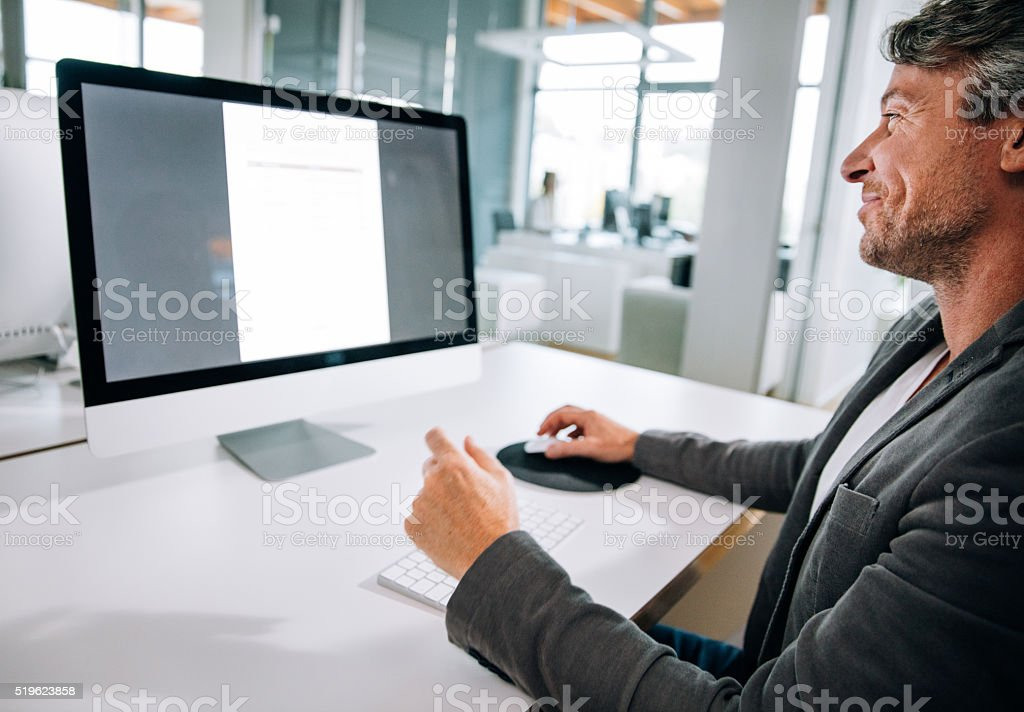 Mature Professional Businessman typing on keyboard in office stock photo