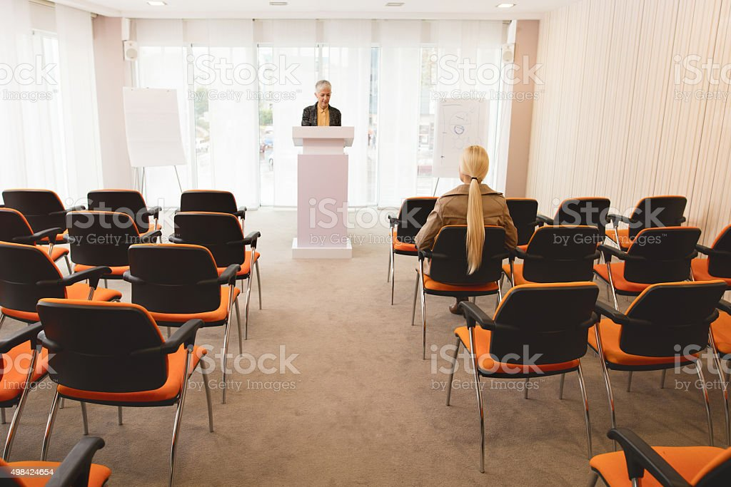 Mature professor having class with one student in lecture hall. stock photo