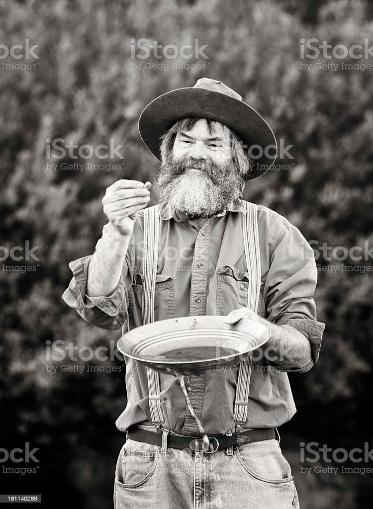 Mature prospector panning for gold vertical stock photo