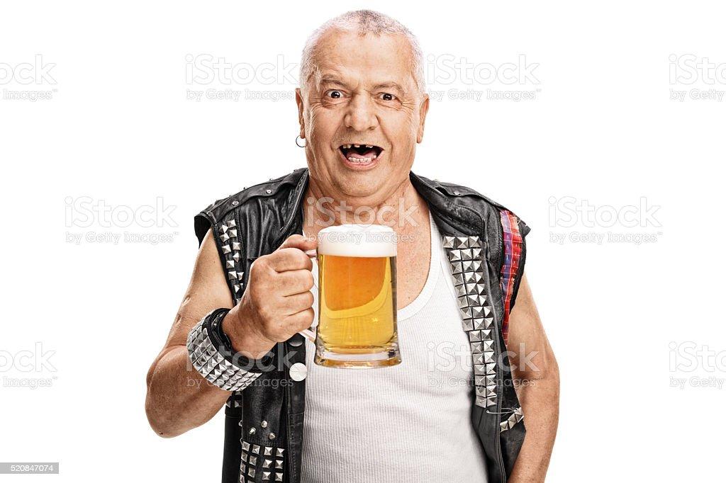 Mature punk rocker holding a pint of beer stock photo