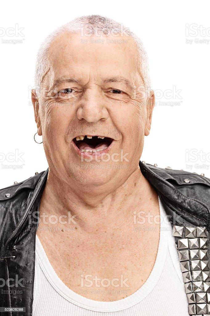 Mature punk rocker with a few broken teeth stock photo