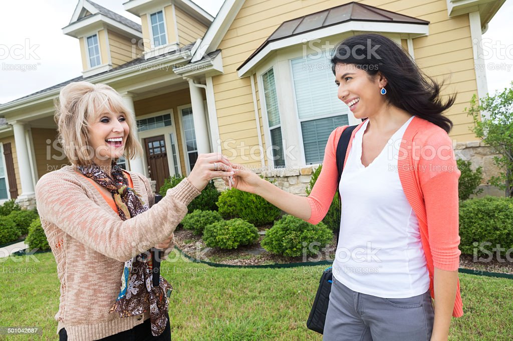 Mature real estate agent giving house keys to excited homeowner stock photo