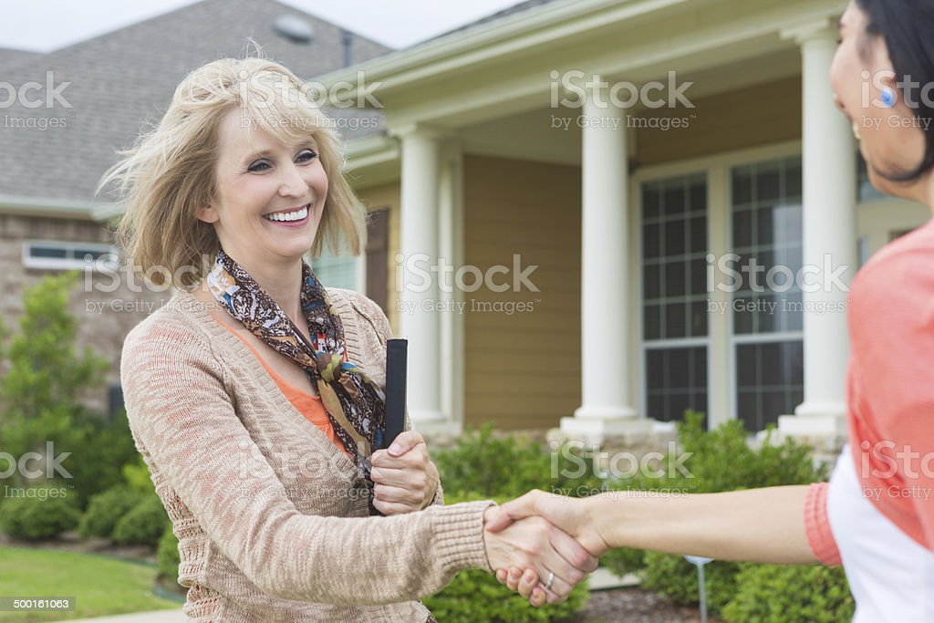 Mature real estate agent meeting future homeowner stock photo