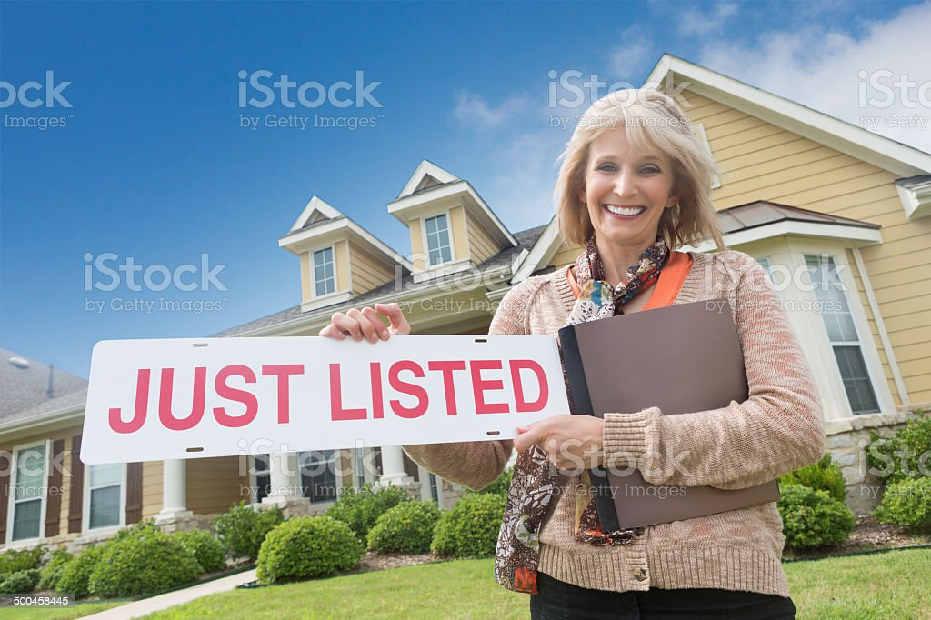 Mature realtor holding 'just listed' sign in front yard stock photo