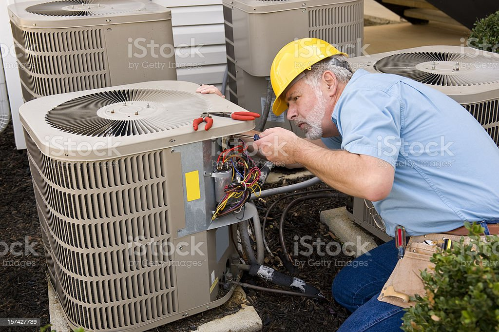 Mature Repairman Works On Apartment Air Conditioning Unit royalty-free stock photo