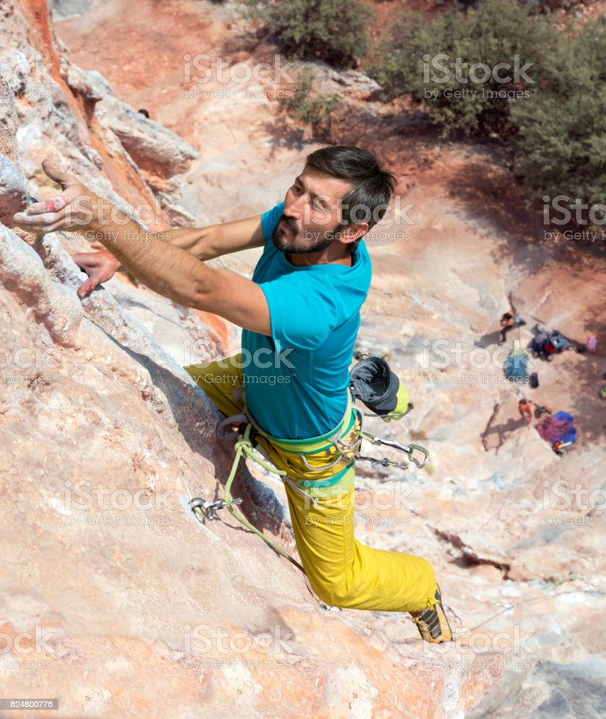 Mature Rock Climber hanging on vertical Wall high above Ground stock photo