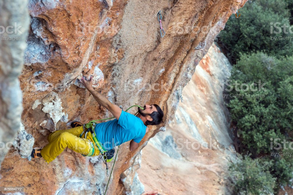 Mature Rock Climber holds rope in teeth stock photo