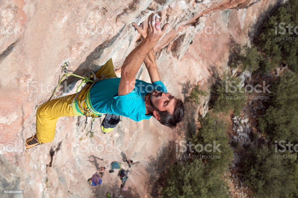 Mature Rock Climber makes a difficult move on overhanging Wall stock photo