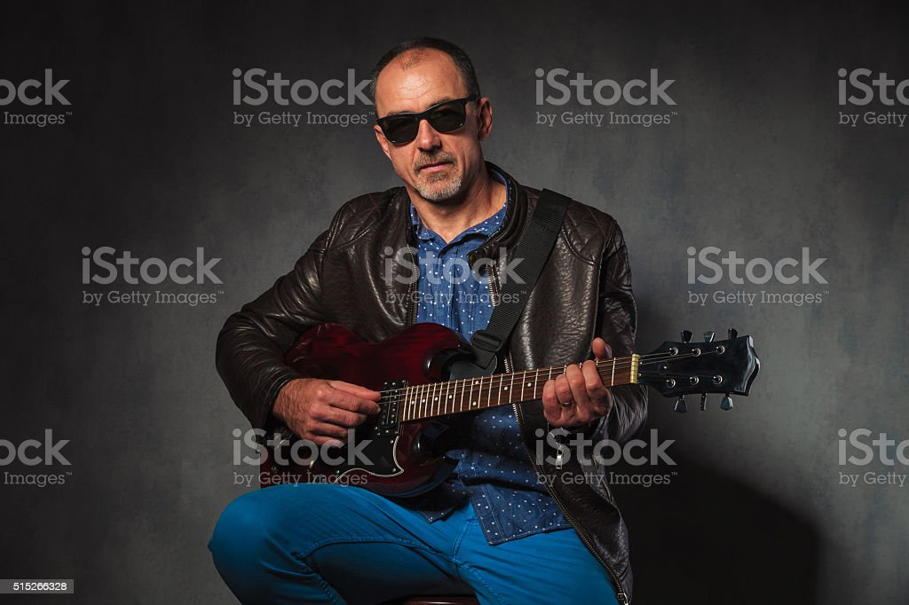 mature rocker in leather jacket playing electric guitar stock photo