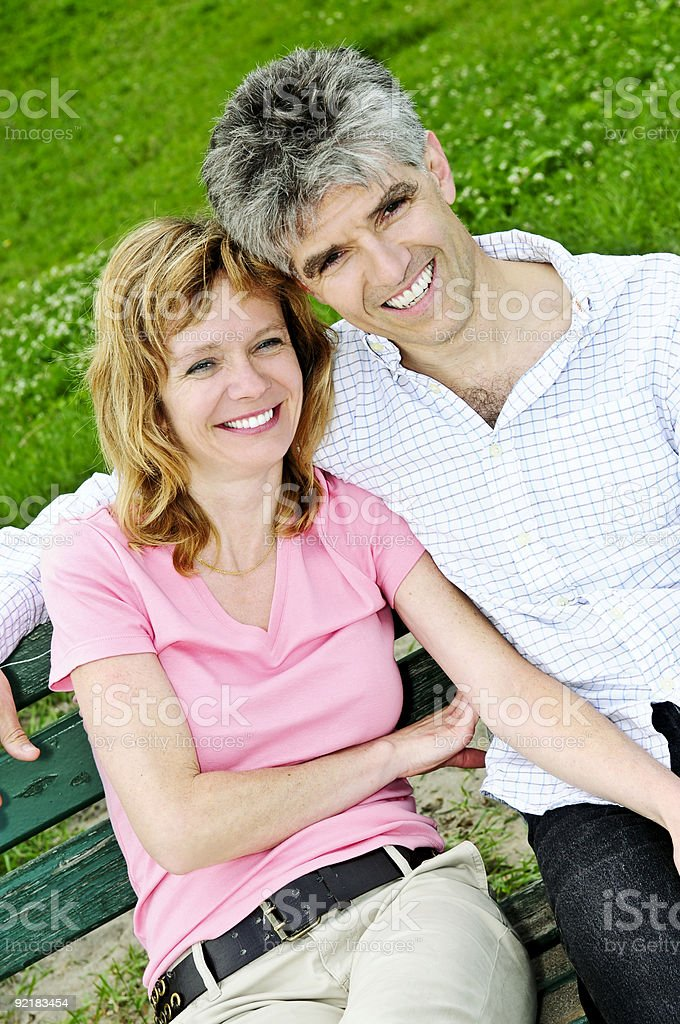 Mature romantic couple on a bench royalty-free stock photo