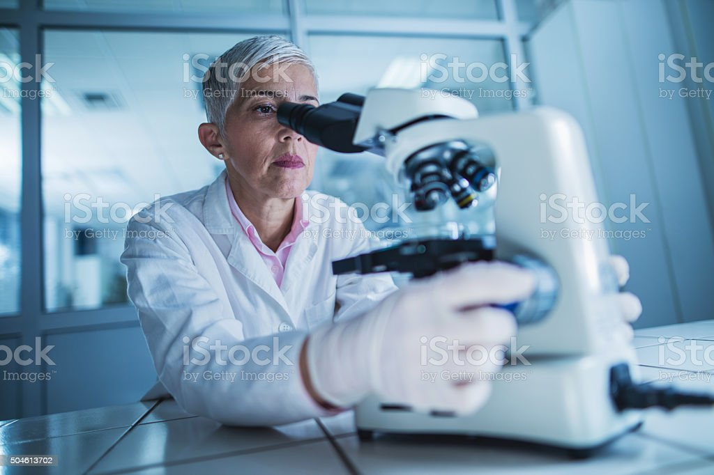 Mature scientist looking through a microscope in a laboratory. stock photo