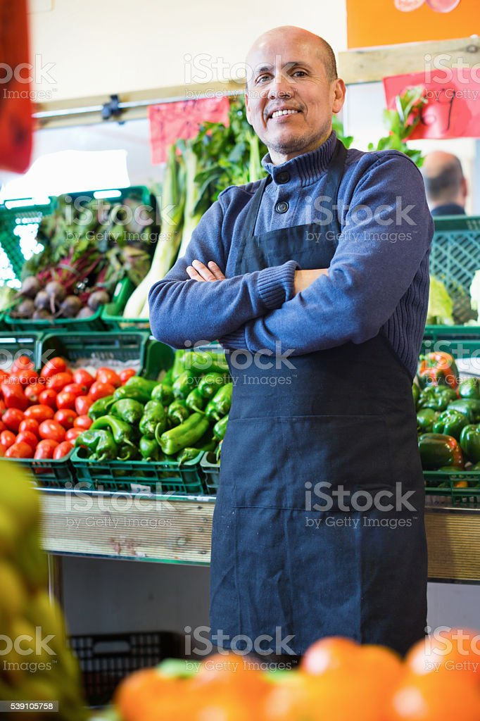 Mature seller offering seasonal vegetables in local grocery stock photo