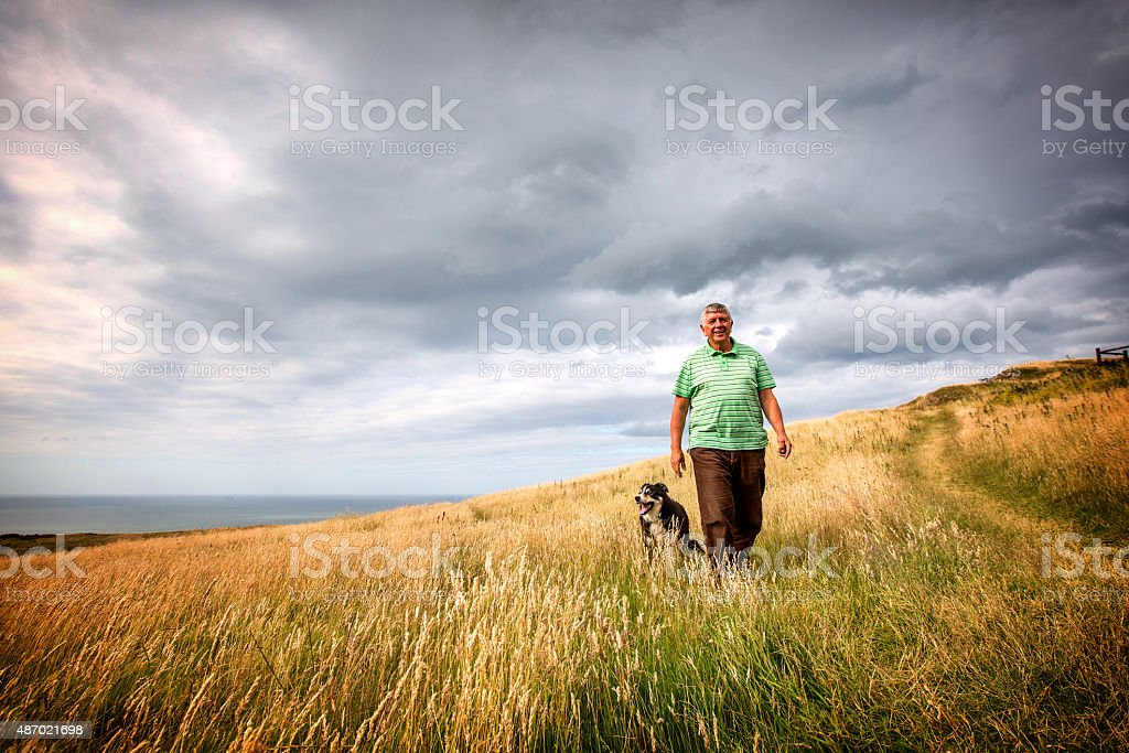 Mature senior man walking on coastal headland with sheepdog stock photo