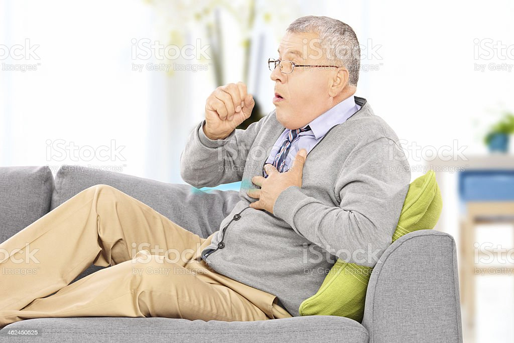 Mature sick man coughs sitting on the grey sofa stock photo