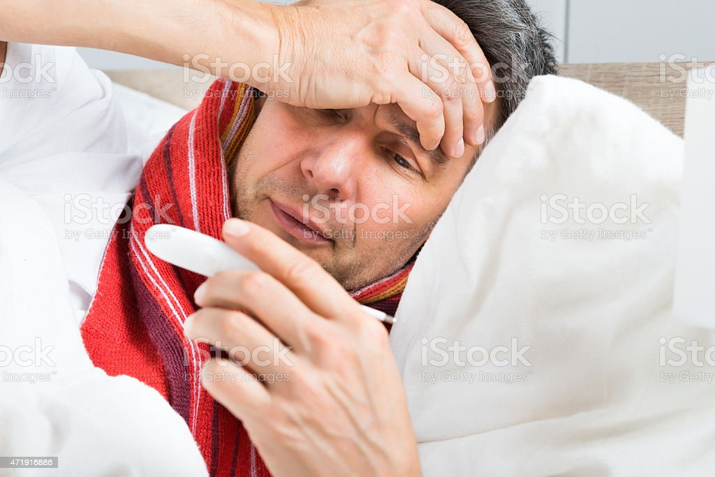 Mature Sick Man Holding A Thermometer stock photo