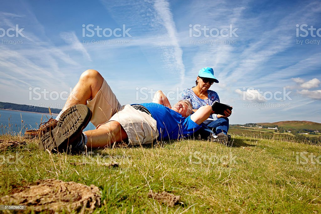 Mature smiling couple relaxing on coastal headland with Tablet PC stock photo