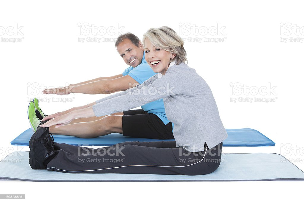 Mature smiling couple, seated and reaching for their toes stock photo
