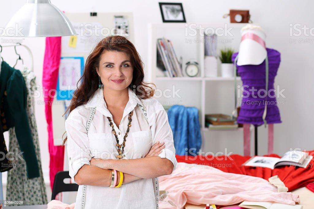 Mature smiling female fashion designer standing in workshop port stock photo
