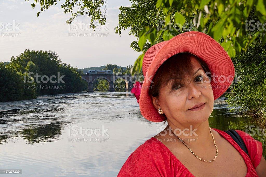 Mature smiling hispanic woman in sunhat on Dordogne River stock photo