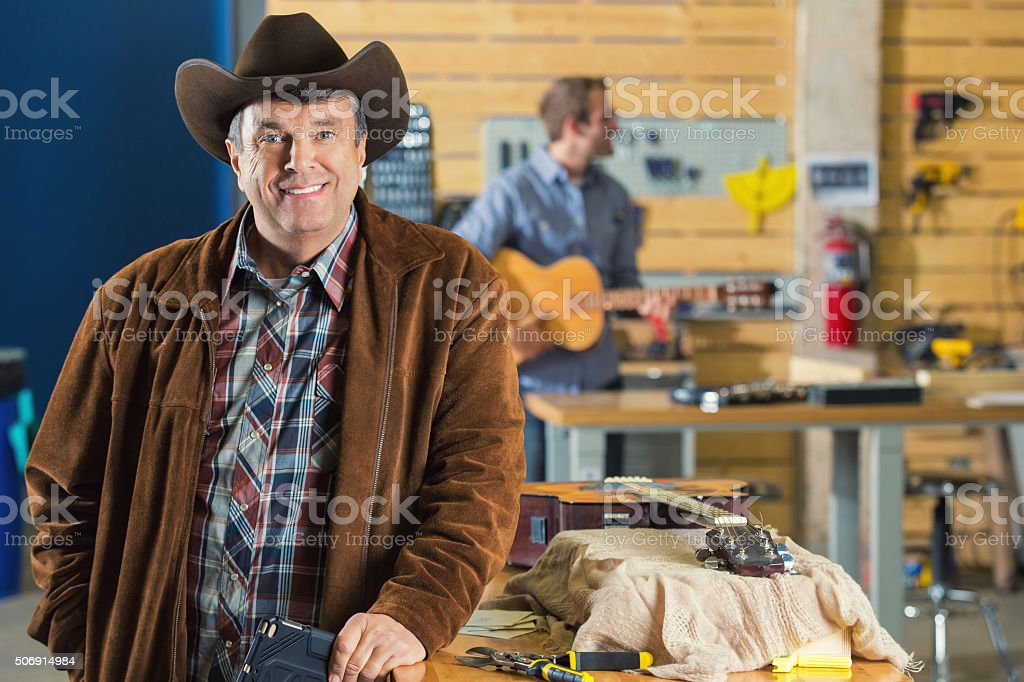 Mature southern businessman in music repair workshop stock photo