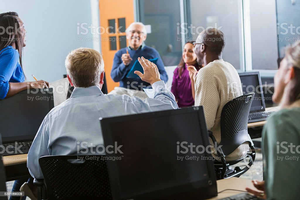 Mature student in class raising hand stock photo