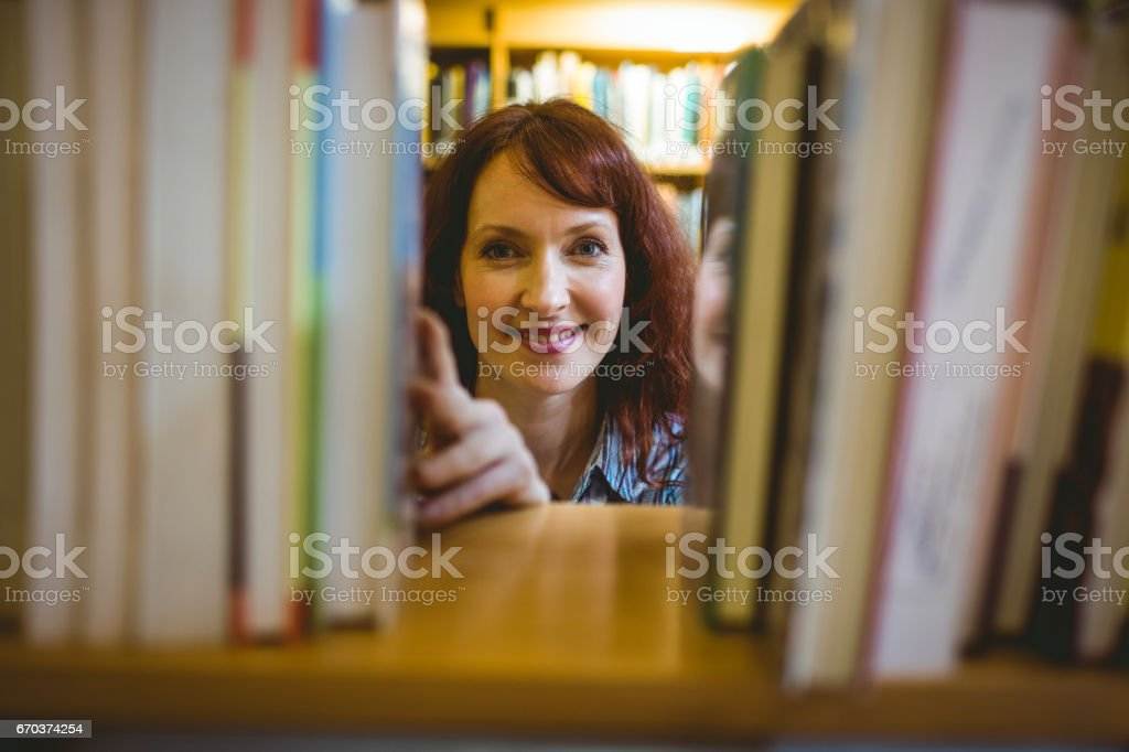 Mature student picking out book in library stock photo