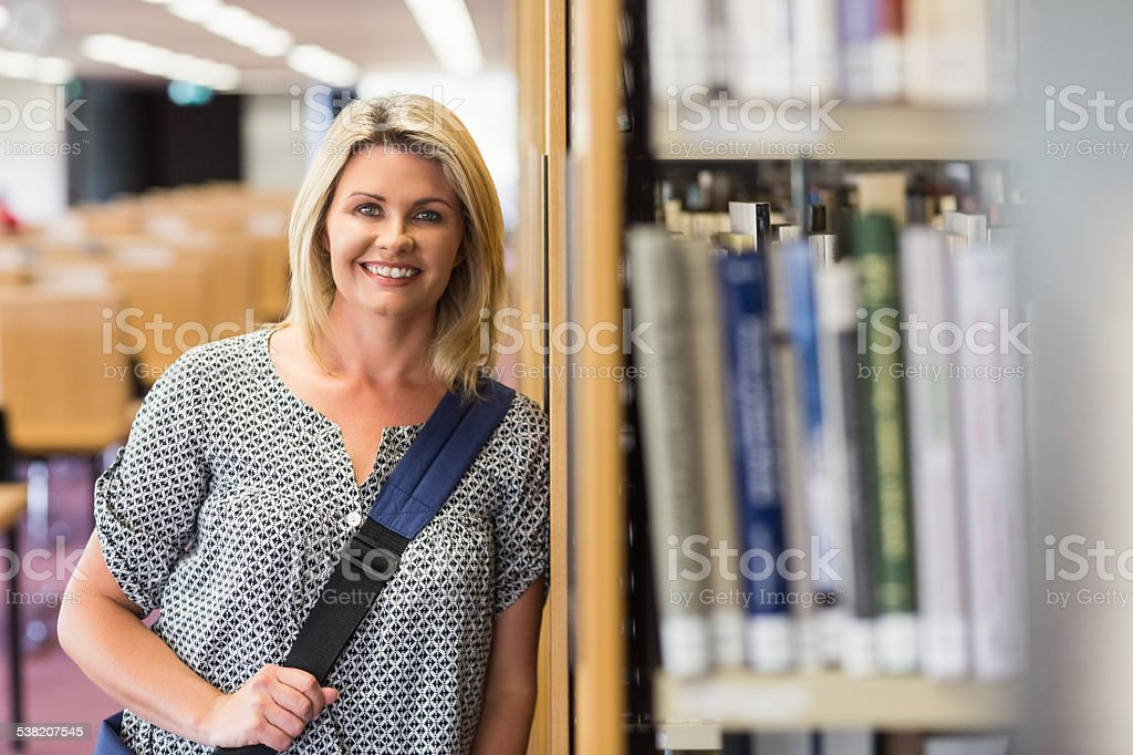 Mature student studying in the library with tablet stock photo