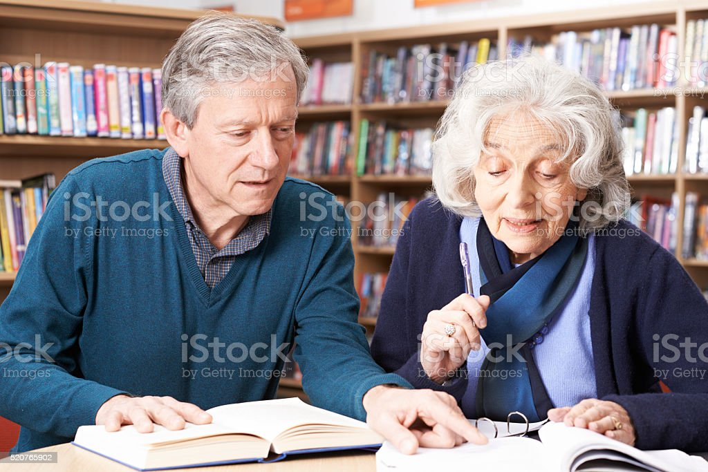 Mature Student Working With Teacher In Library stock photo